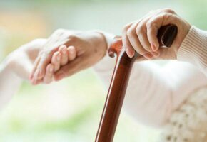 Mladá ruka podává pomocnou ruku seniorce s hůlkou.