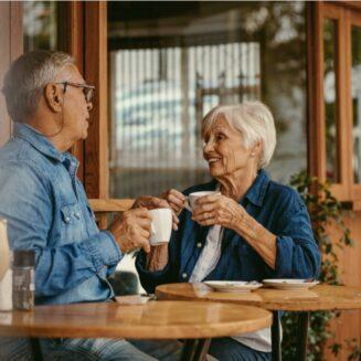 Seniorní pár popíjí kávu ve stylové kavárně.