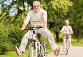 Veselý starší pán jede na kole a radostí zvedá nohy do vzduchu.