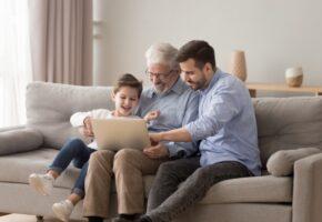 Dědeček, otec a syn společně sedí na gauči, drží laptop a smějí se.