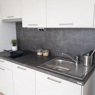 Bílá, moderní kuchyňská linka s tmavou pracovní deskou.