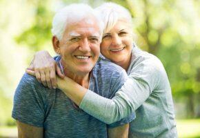 Paní objímá staršího pána a společně se smějí.