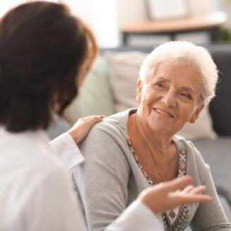 Ošetřovatelka sedící zády promlouvá ke starší ženě, která se na ni usmívá.
